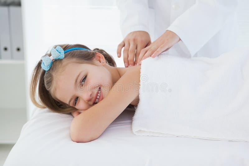 Petite fille de sourire se trouvant sur une table images stock