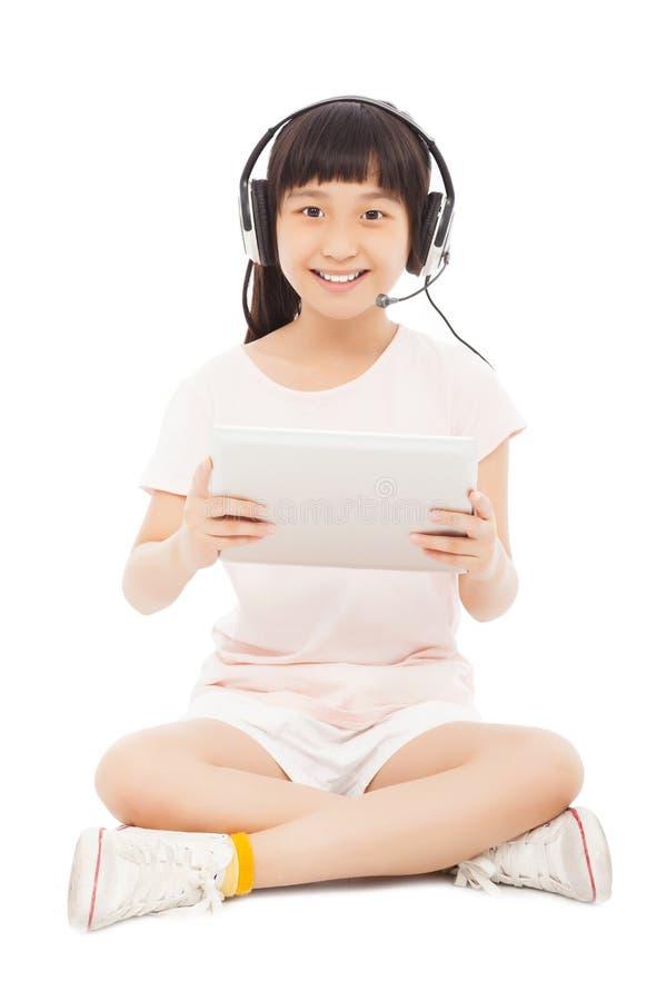 Petite fille de sourire stiiting et tenant un comprimé avec l'écouteur photo stock
