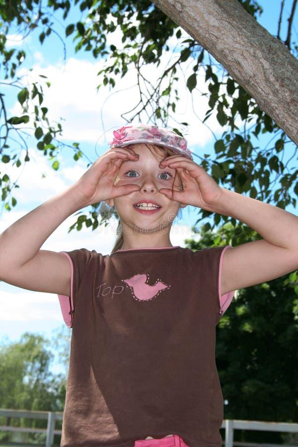Petite fille de sourire sur un fond de ciel bleu photographie stock