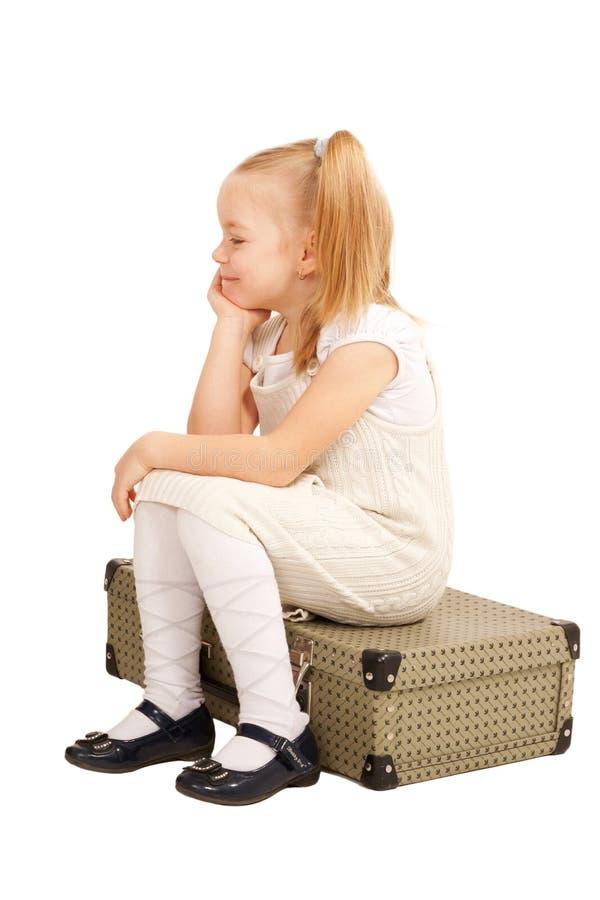 Petite fille de voyageur s'asseyant sur la valise image libre de droits
