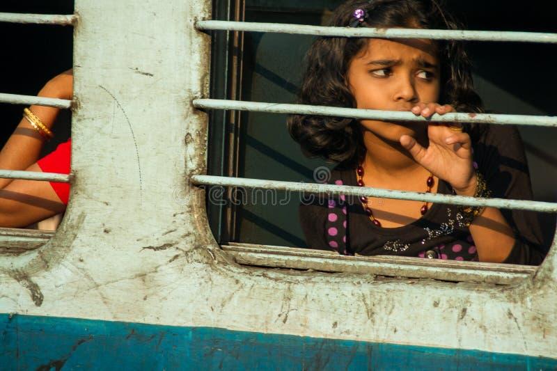 Petite fille derrière des barres de train image stock