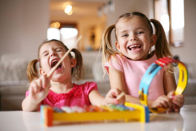 Petite fille deux à l'école de musique photos stock