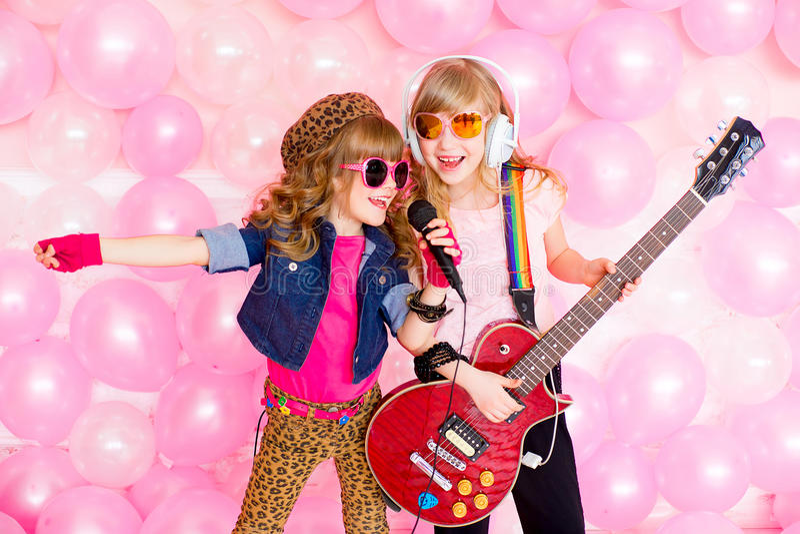 Petite fille deux avec un microphone photos stock