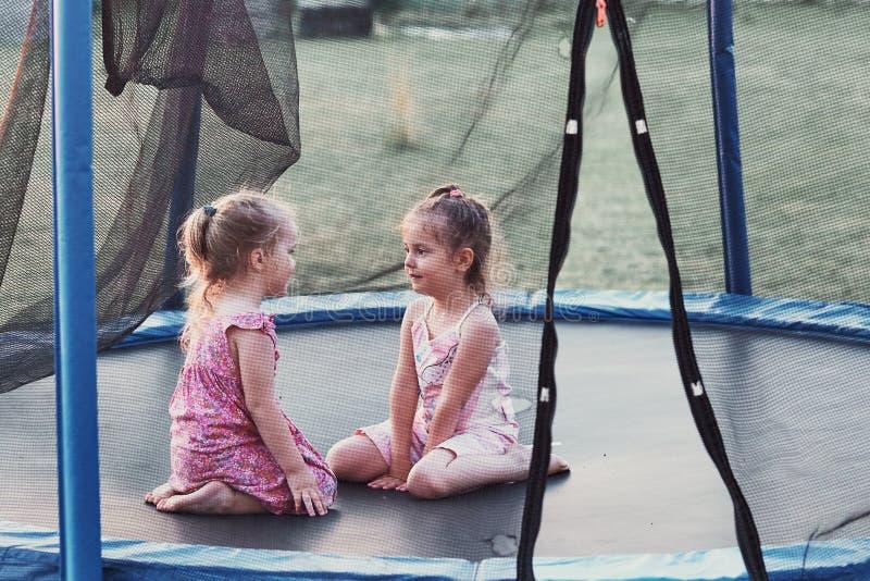 Petite fille deux mignonne jouant sur le trempoline dans l'arrière-cour images libres de droits