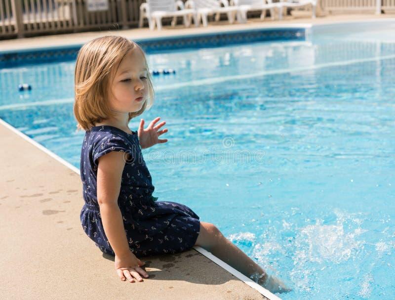 Petite fille donnant un coup de pied l'eau dans une piscine photographie stock