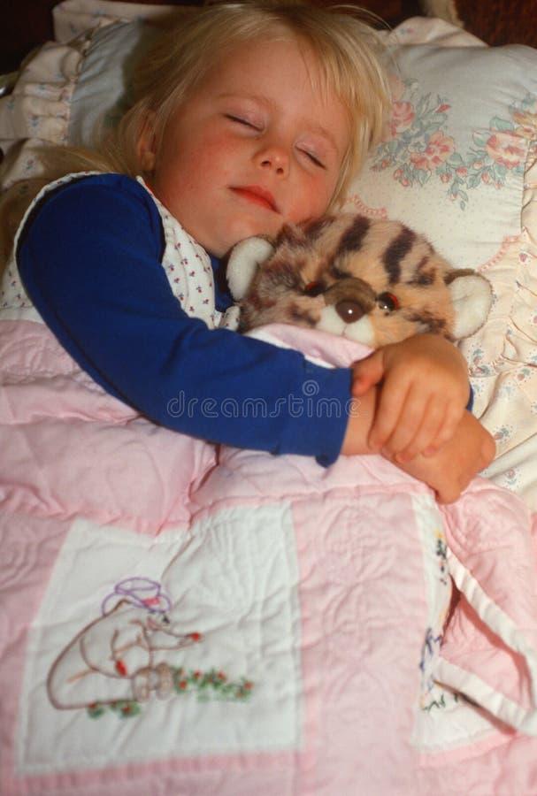 Petite fille dormant avec l'ours de nounours photos libres de droits