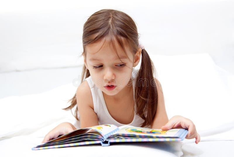 Petite fille douce affichant un livre images libres de droits