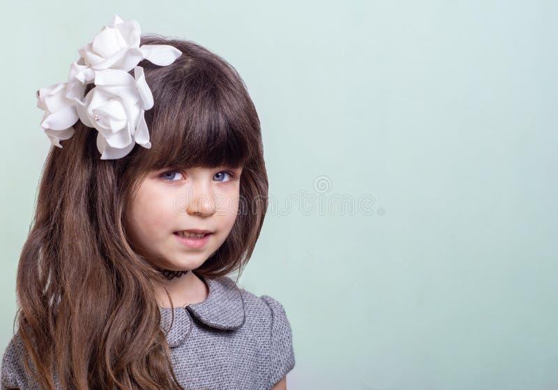 Petite fille douce avec les cheveux bouclés et les fleurs blanches dans la coupe de cheveux Enfant élégant mignon sur le fond ble images libres de droits