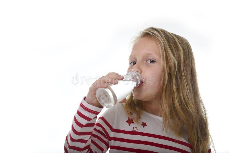 Petite fille douce mignonne avec des yeux bleus et des cheveux blonds 7 années tenant la bouteille de boire de l'eau photographie stock libre de droits