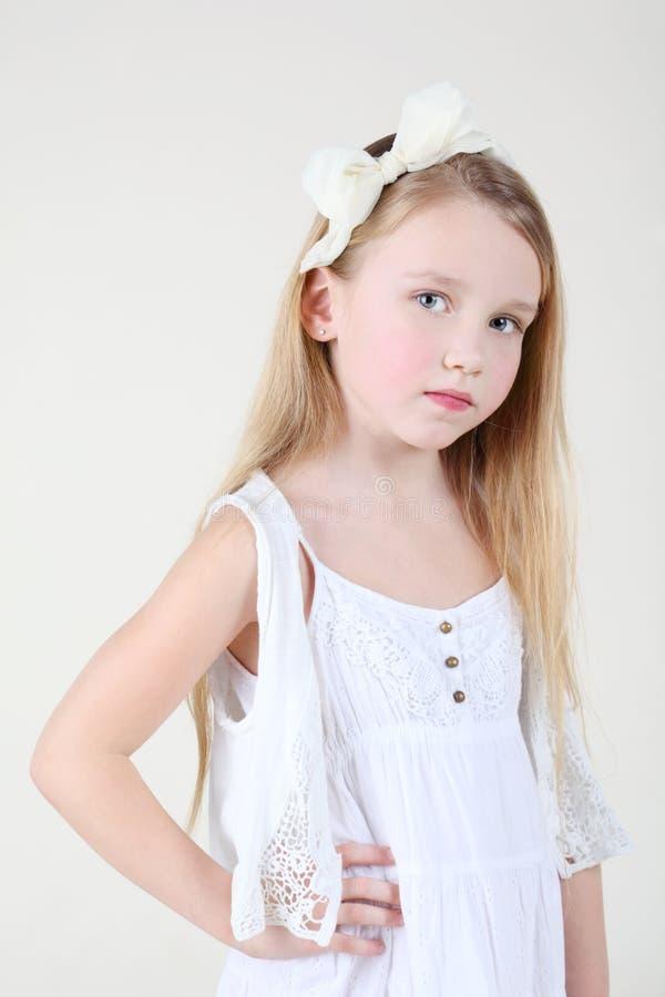 Petite fille douleureuse dans la robe blanche propre avec la proue dans son cheveu image stock