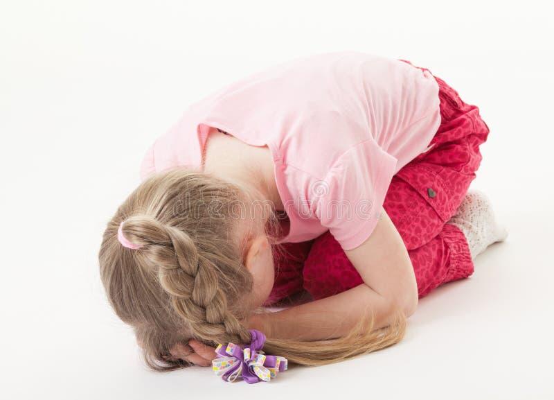 Petite fille douleureuse sur le plancher photo libre de droits