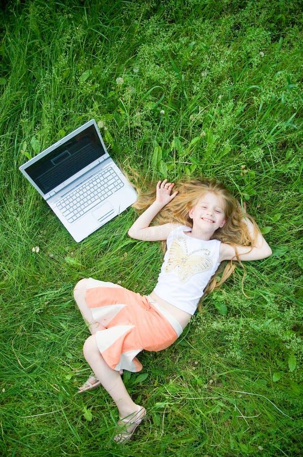 Petite fille drôle avec l'ordinateur portatif à l'extérieur photos libres de droits