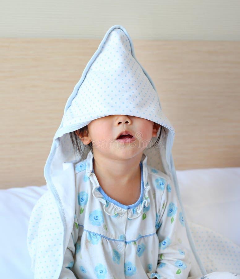 Petite fille drôle avec la couverture couvrante sur la tête se trouvant sur le lit images libres de droits