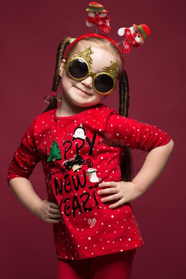 Petite fille drôle dans l'image du ` s de nouvelle année, montrant différentes émotions images stock