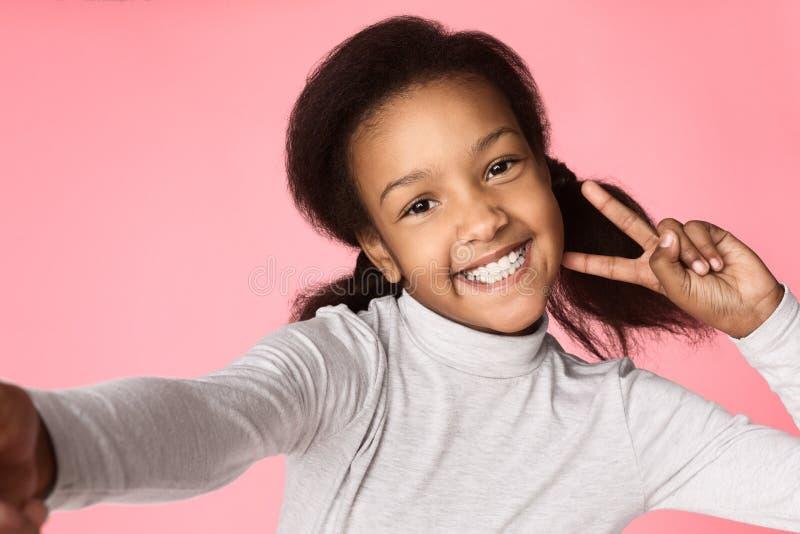 Petite fille drôle grimaçant et prenant le selfie photographie stock libre de droits