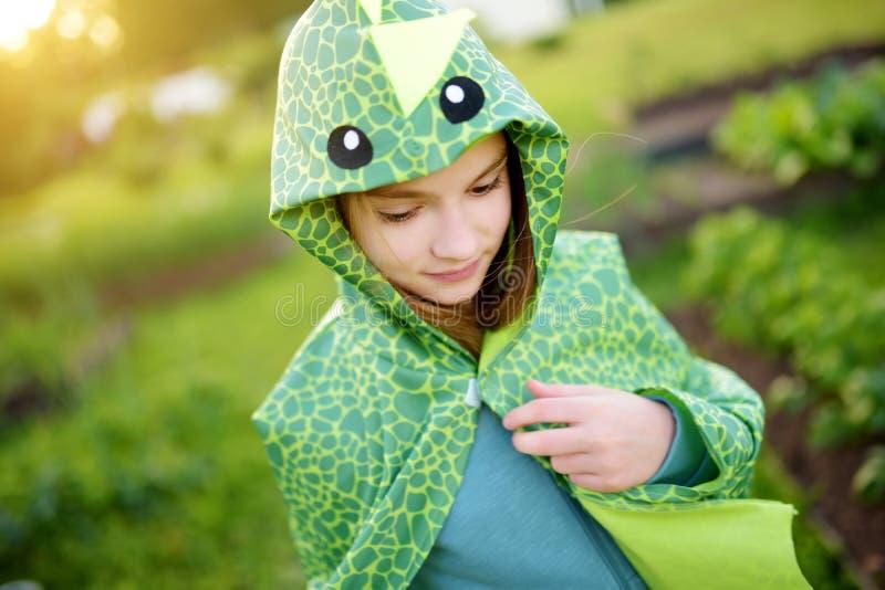 Petite fille drôle habillée comme dragon ayant l'amusement dehors le jour d'été photos stock