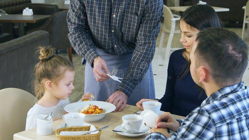 Petite fille drôle jouant avec son jouet avant de manger son dîner en café avec ses parents Le serveur lui apporte une prise photographie stock libre de droits