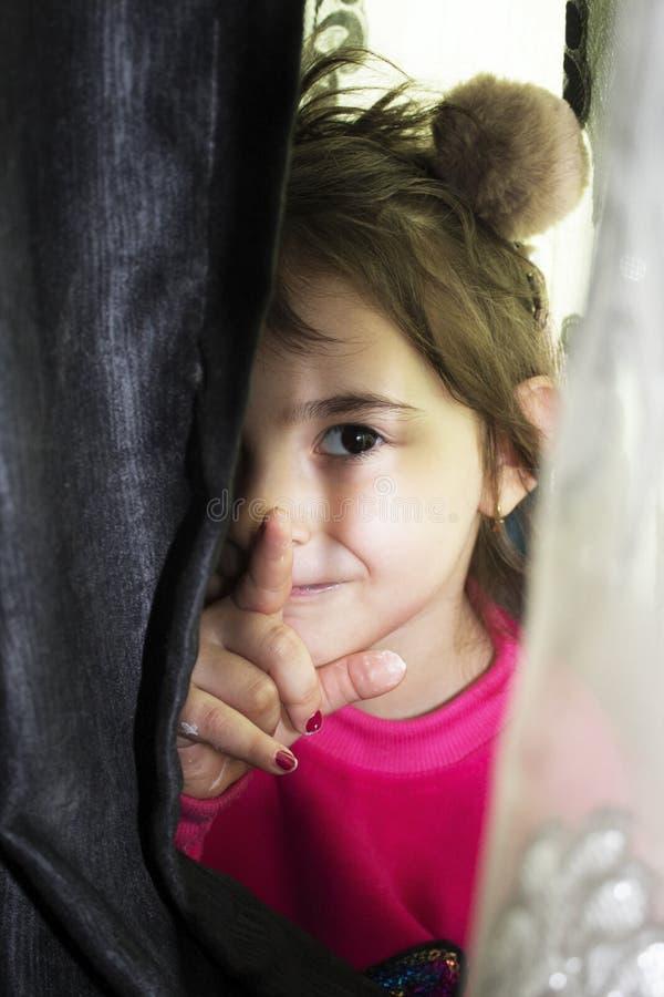 Petite fille drôle jouant le jeu caché photos stock