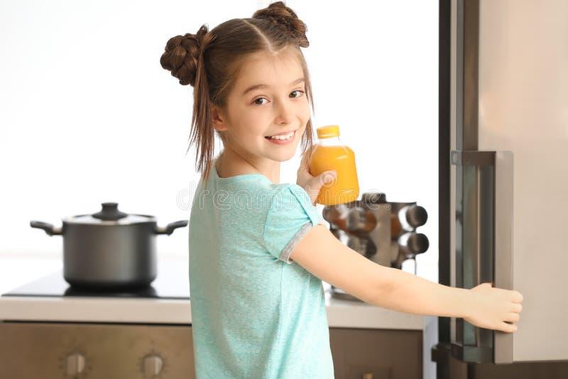 Petite fille drôle prenant le pot avec le jus d'agrumes du réfrigérateur dans la cuisine image libre de droits