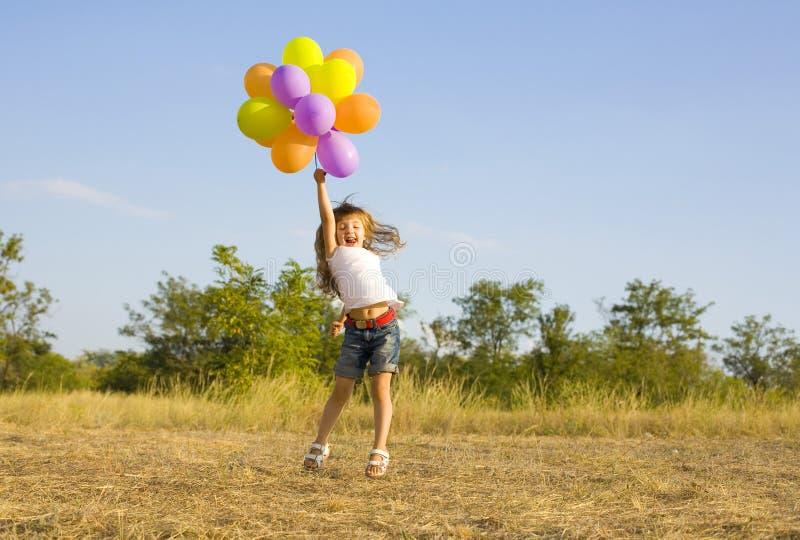 Petite fille drôle avec des ballons, rebondissant image libre de droits