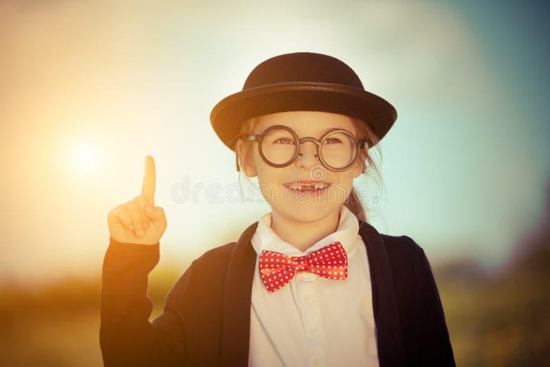 Petite fille drôle dans le chapeau en verre, de noeud papillon et de lanceur photographie stock