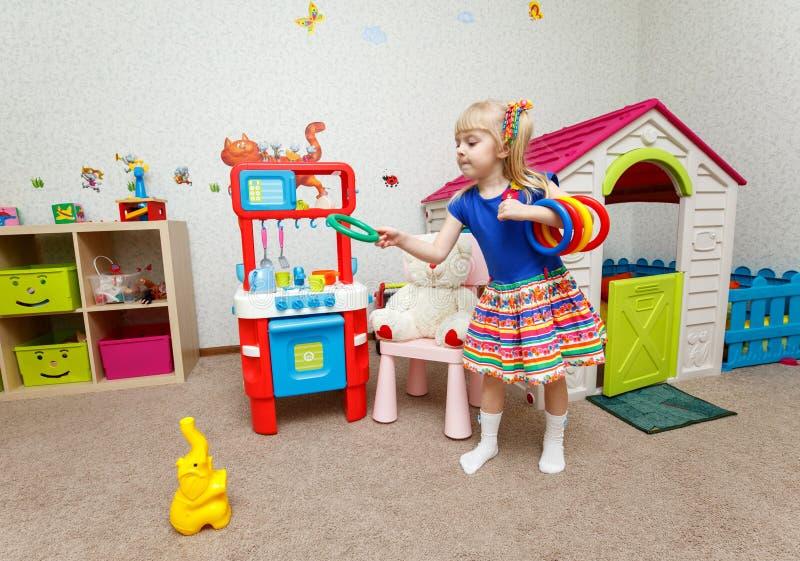 Petite fille drôle jetant les anneaux en plastique sur l'éléphant de jouet photographie stock