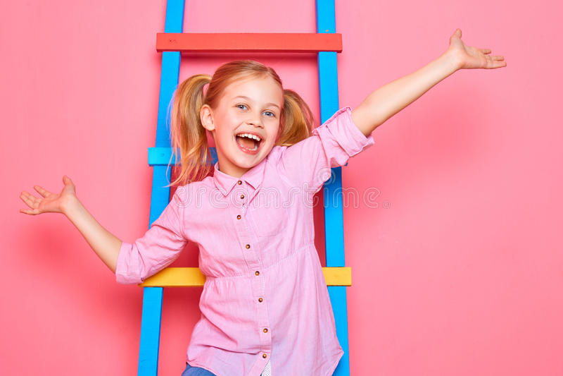 Petite fille drôle s'asseyant sur les escaliers, les mains de ondulation et rire image stock