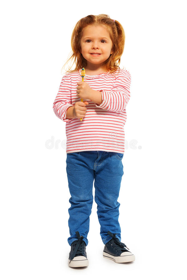 Petite fille drôle tenant la brosse à dents jaune images stock