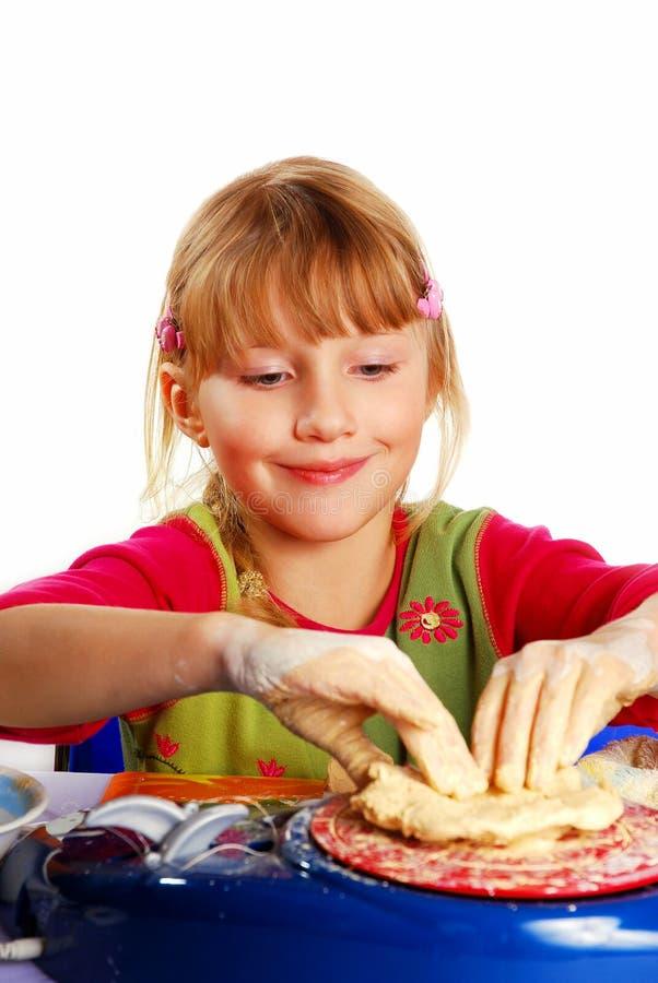 Petite fille effectuant la poterie photos stock