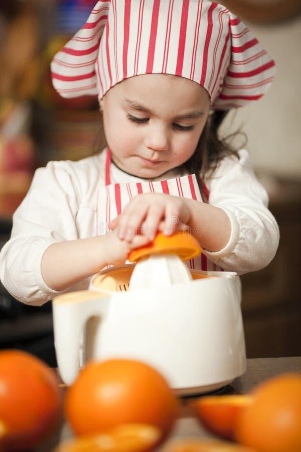 Petite fille effectuant le jus frais image stock
