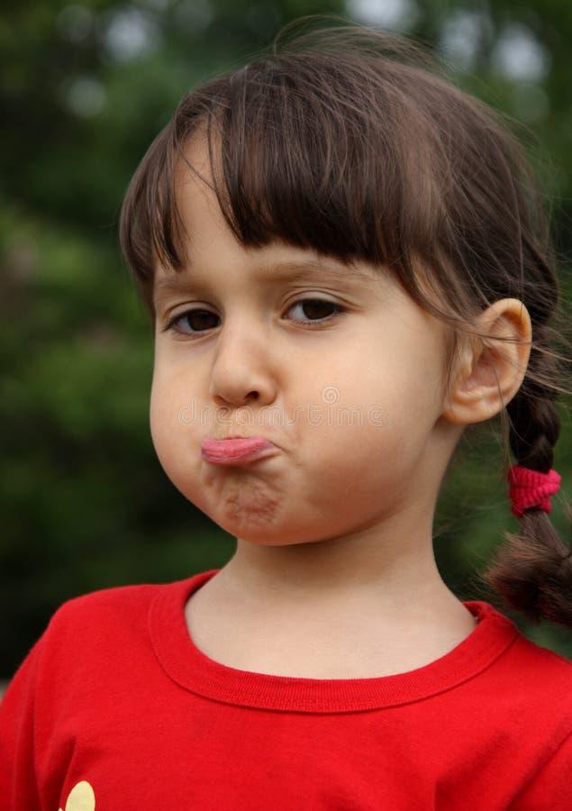 Petite fille effectuant le visage drôle photographie stock libre de droits
