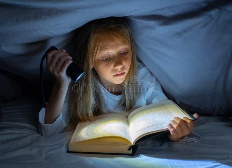 Petite fille effrayée lisant le livre effrayant sous le couvre-lit tenant une lampe-torche tard la nuit photo stock