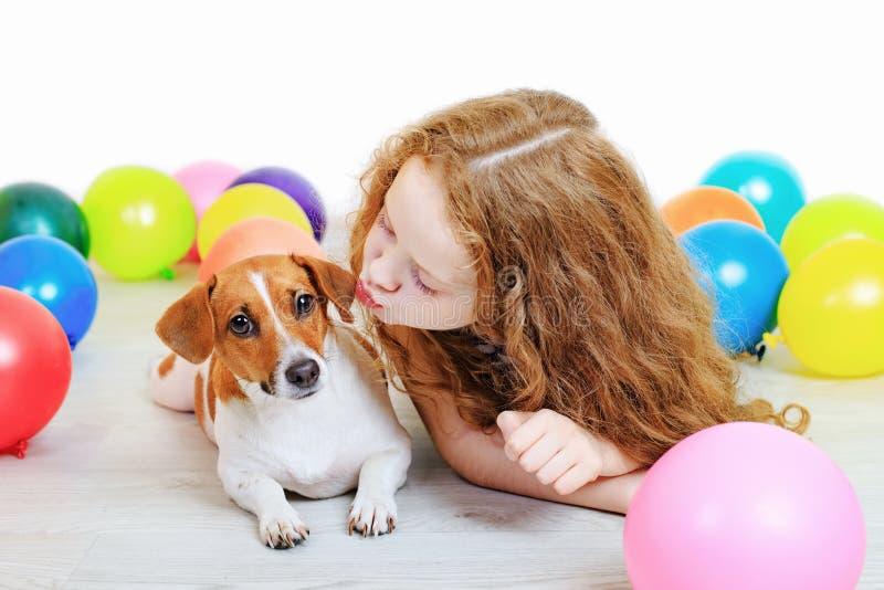 Petite fille embrassant avec son terrier de Russell de cric dans la PA d'anniversaire photo libre de droits