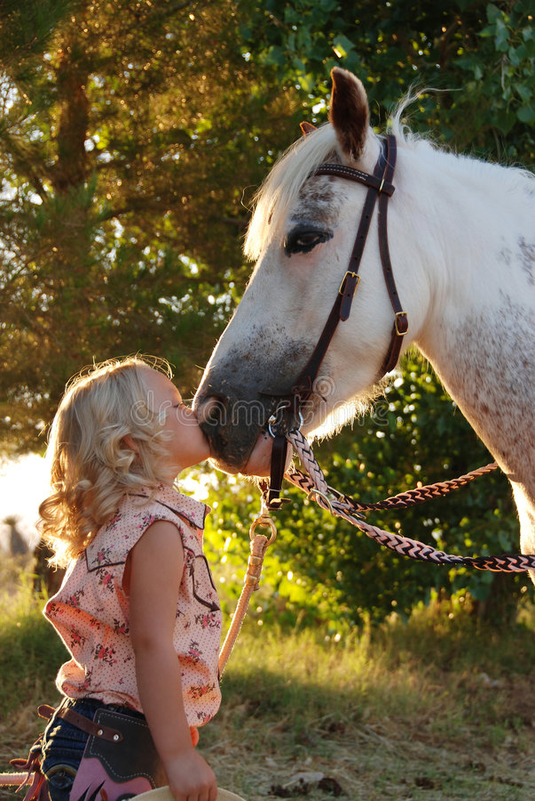 Petite fille embrassant le poney. photo stock