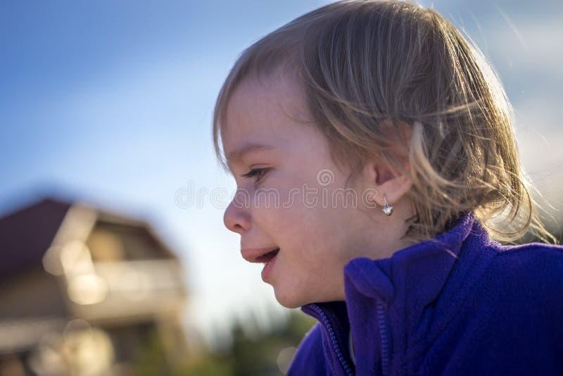 Petite fille en désordre pleurant dehors photographie stock libre de droits