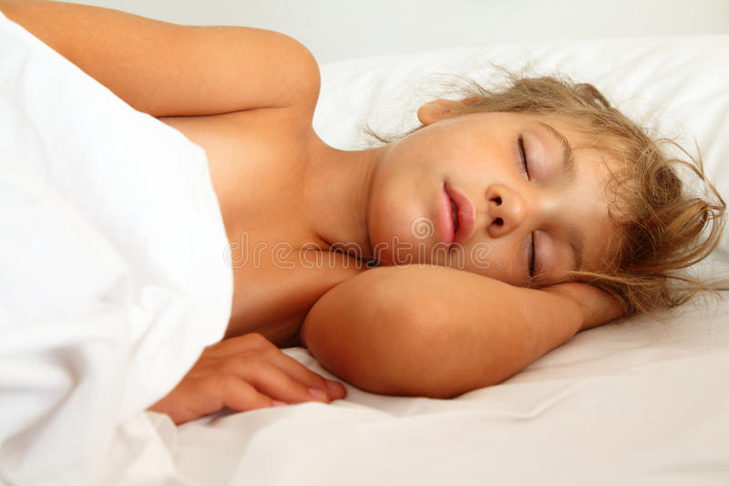 Petite fille en sommeil dans le bâti sur la feuille et l'oreiller photos libres de droits
