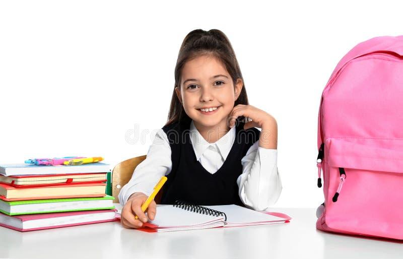 Petite fille en uniforme en affectation à un bureau arrière-plan blanc Stations scolaires photos stock