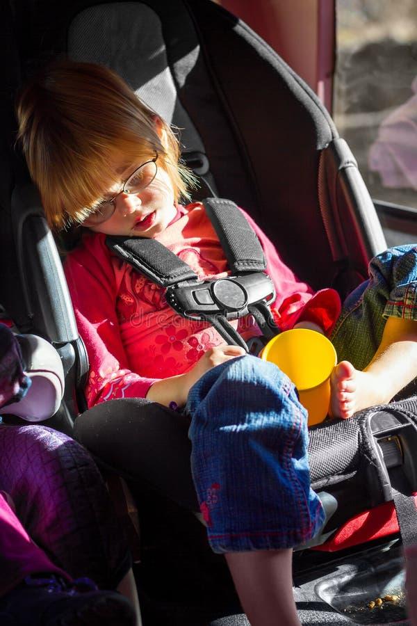 Petite fille endormie et radotante dans son Carseat sur une promenade en voiture images libres de droits