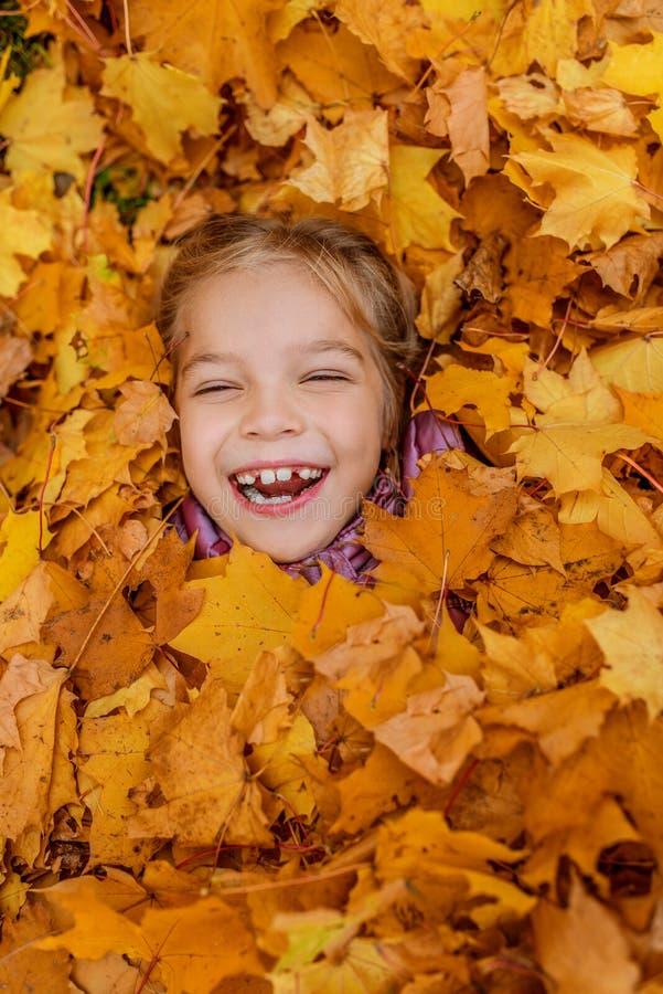 Petite fille enterrée dans le jaune de feuilles d'automne photographie stock