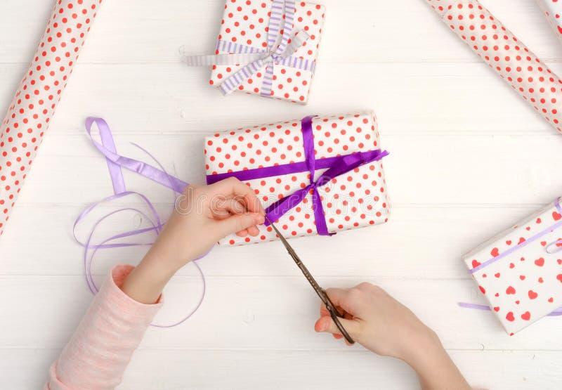 Petite fille enveloppant des cadeaux pendant des vacances image libre de droits