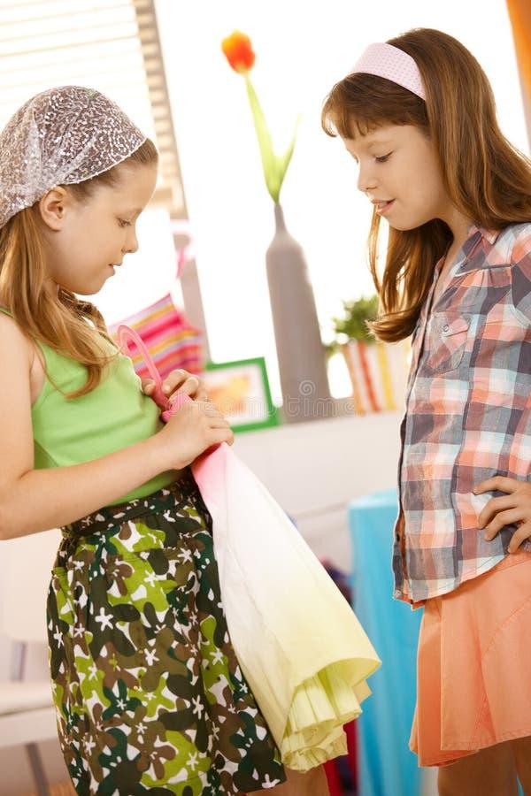 Petite fille essayant sur la jupe à la maison image stock