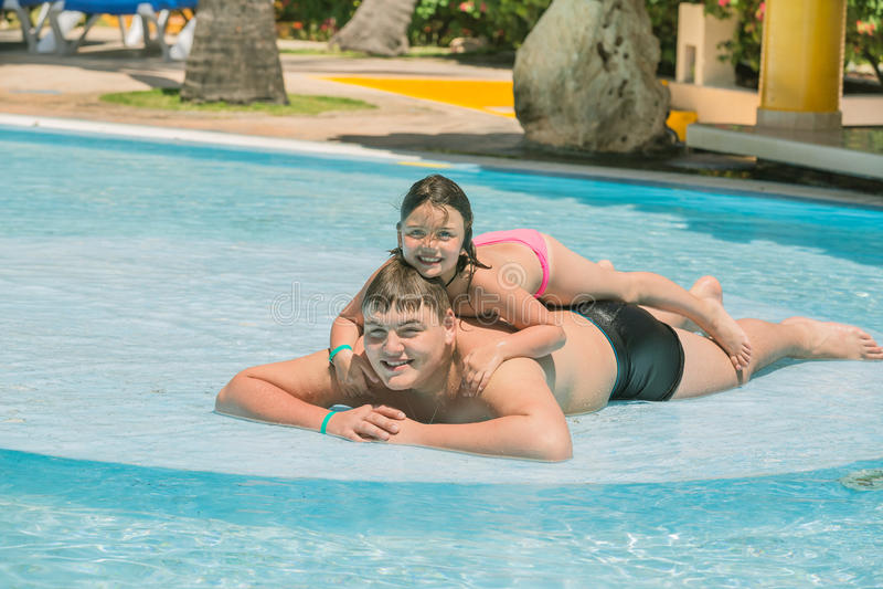 Petite fille et adolescent ayant l'amusement dans la piscine de jardin le jour chaud ensoleillé image stock