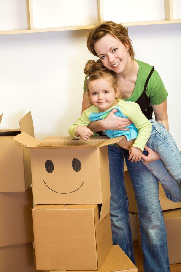 Petite fille et femme avec des boîtes en carton image stock