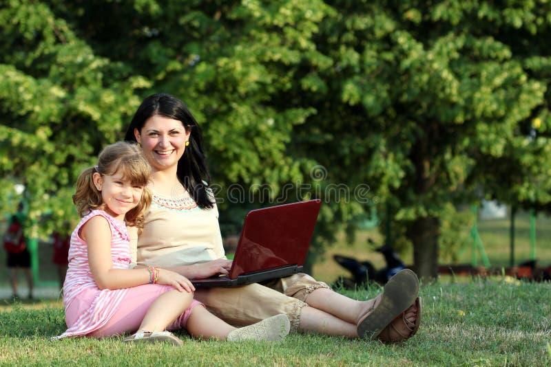 Petite fille et femme avec l'ordinateur portable en parc photo libre de droits