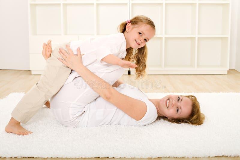 Petite fille et femme jouant à l'intérieur sur l'étage photos stock