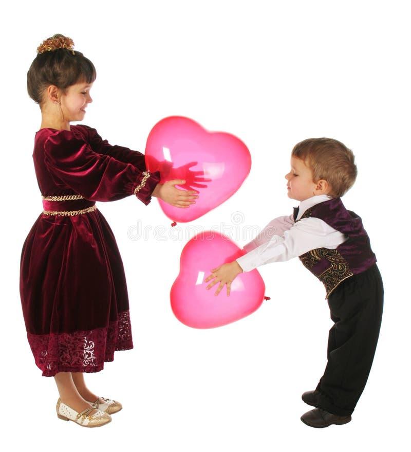 Petite fille et garçon avec le rouge coeur-comme des ballons photos stock