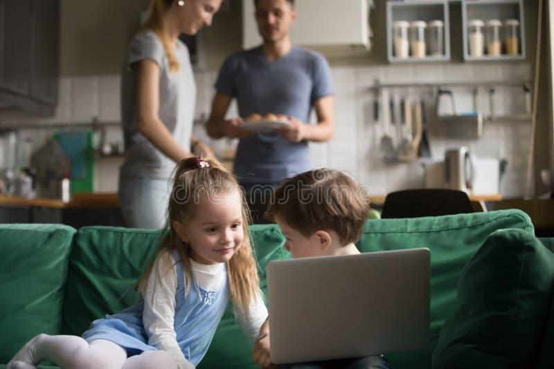 Petite fille et garçon employant la cuisson de parents de moment d'ordinateur portable photo stock