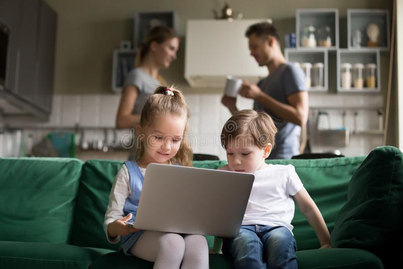 Petite fille et garçon employant parler de parents de moment d'ordinateur portable photos stock
