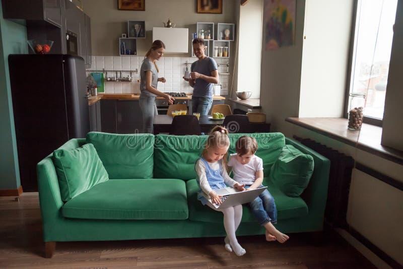 Petite fille et garçon employant parler de parents de moment d'ordinateur portable image libre de droits