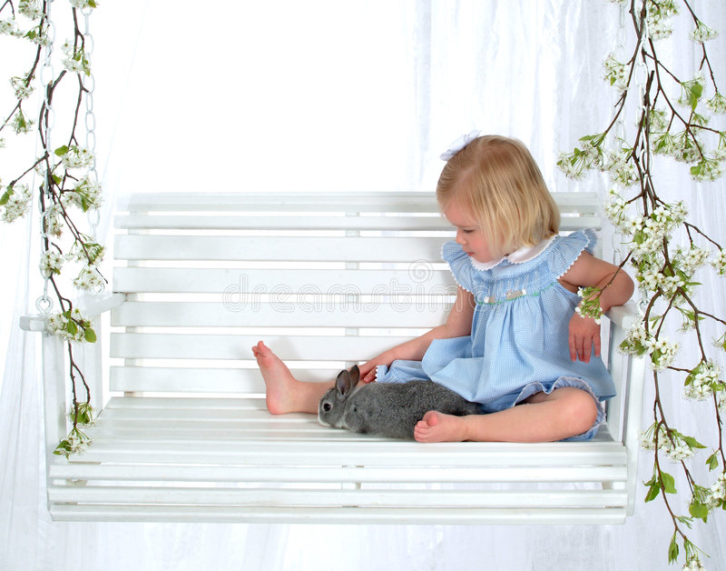 Petite fille et lapin sur l'oscillation images stock